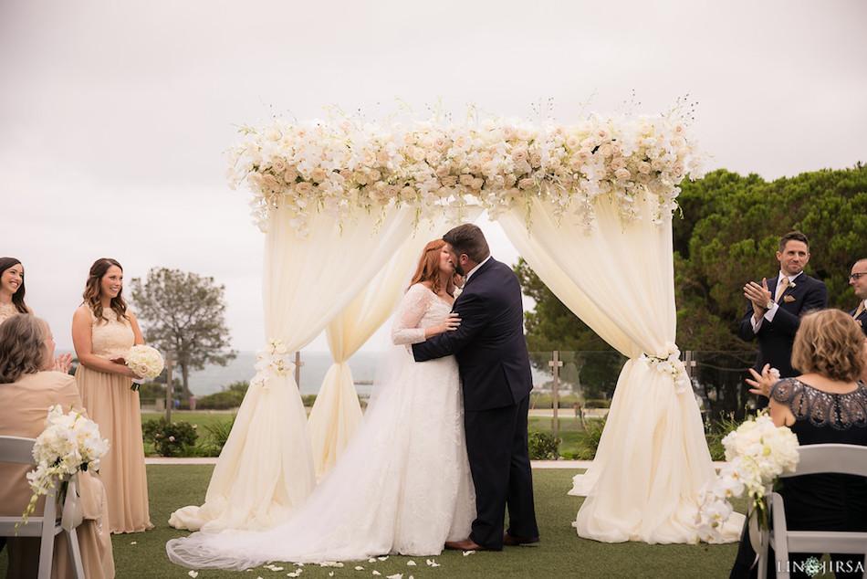 first kiss, newlyweds, bride, groom, arch, wedding flowers, enchanting laguna cliffs marriott, flowers by cina