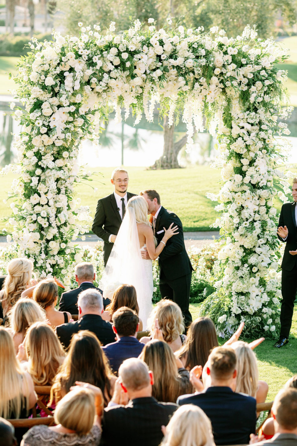first kiss, bride and groom, floral-filled arch, exquisite white wedding, floral design, florist, wedding florist, wedding flowers, orange county weddings, orange county wedding florist, orange county florist, orange county floral design, flowers by cina